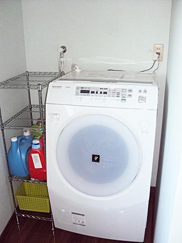 以前あった洗濯パンを取り止め排水金物にし、スッキリとしたユーティリティーとなりました。空きスペースにはラックが置かれ、空間をうまくご利用いただいています。