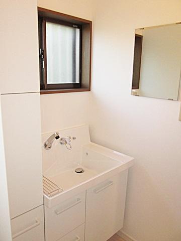 洗面所は、LIXILのピアラを採用。ホワイトが基調となり爽やかな印象となりました。背の高いサイドキャビネットで、収納も充実しています。