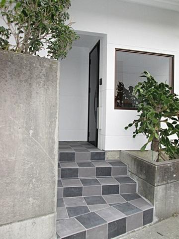 玄関サッシを取り替え、床タイルを貼り替えました。市松模様のタイルとブラックのサッシでモダンなアプローチになりました。