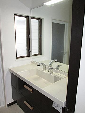 洗面化粧台も落ち着いた色合いで、余裕のあるカウンターと収納も充実したものとなりました。