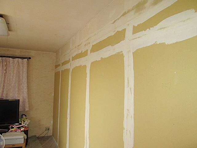 造作した間仕切り壁のジョイント部分にパテを塗り、ビニールクロスの下地処理を行っています。クロス貼りを行いました。