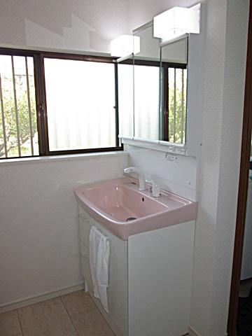 洗面所は、クロスのドット柄と洗面化粧台を同系色で合わせて、可愛らしい印象の空間となりました。