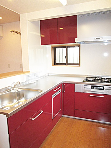 新しいキッチンは、ワインレッドが映える明るく素敵なキッチンとなりました。対面式キッチンで家族の対話を楽しみながら家事も楽しく行えます。