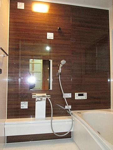 在来工法の浴室から、スタイリッシュな雰囲気のユニットバスに変更をしました。木目調の落ち着いた色合いのアクセントパネルで、快適な空間に生まれ変わりました。