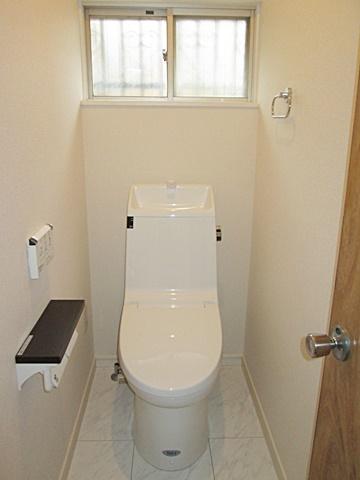 こちらは玄関横のトイレです。タイル張りの和式トイレから洋式トイレに変更しました。シンプルで使い易くお手入れも楽な便器で、明るく快適な空間になりました。