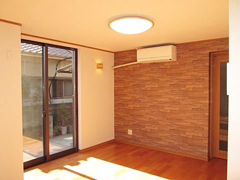 居間もサッシを取り替えて明るい部屋になりました。西面のみ石目調のクロスを貼りアクセントにしています。