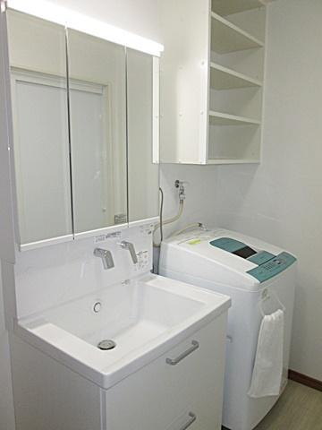 洗面所は白を基調にした衛生的な空間に。洗濯機の上に棚を造り付けたので、収納力も抜群です。