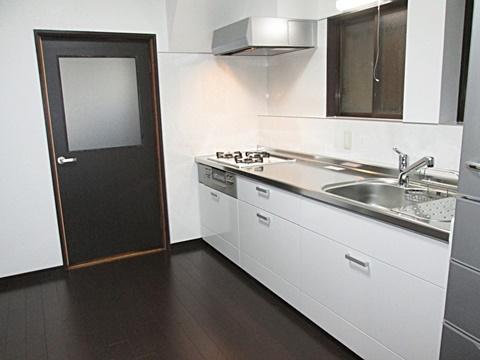 システムキッチンは、シンプルで使い易い物にしました。階段下にレンジフードをはめ込み、右端に冷蔵庫スペースを設けました。