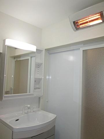 ホワイト色を基調にした洗面所は、明るく衛生的な空間になりました。また、暖房機を設けヒートショック対策も行われています。