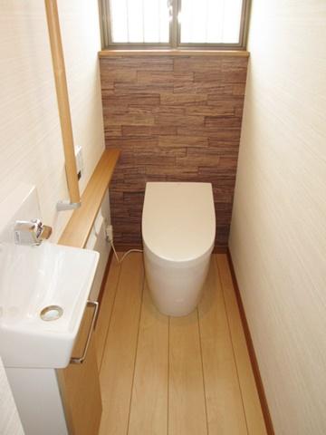 1階トイレです。タンクレスでスッキリとしています。手摺と手洗いを設け使い勝手も考慮されています。正面のアクセントウォールがポイントです。