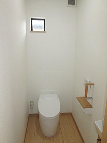 1階のトイレは、ホワイトを基調に明るい個室になりました。タンクレスでスッキリと納まり、ハンドグリップや手洗いを設け使い勝手も考慮しています。